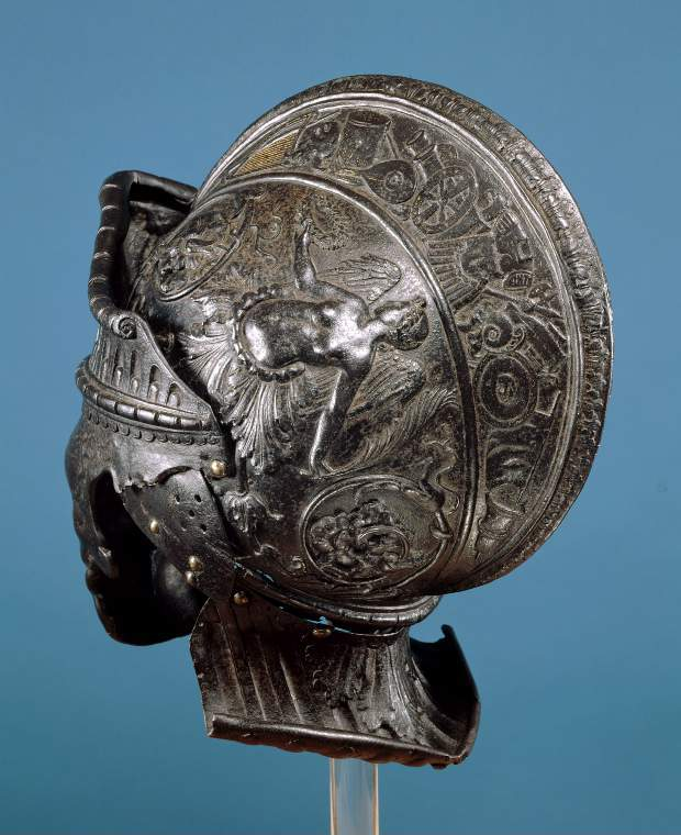 An image of Armour. Burgonet, for parade use, with embossed, chased and counterfeit-damascend classical decoration. Negroli, Filippo, perhaps (Italian armourer, Milanese, c.1510, active 1532-1551). Formed of a one-piece skull with a pivoted 'visor', an incomplete pair of cheek-pieces, and a neck-defence of one lame; hammered, shaped, riveted, with embossed, chased and counterfeit-damascening decoration, pierced ventilation-holes, recessed borders and raised ribs. Low-carbon steel, height (whole) 31.4 cm x width (whole): 20.2 cm. depth (whole) 29.3 cm, c.1540-1545.