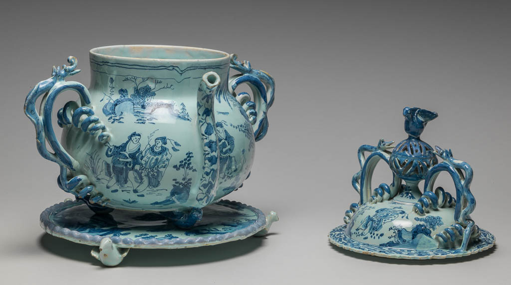 An image of English Delftware. Posset pot with cover and stand (see C.1504 & B-1928). Brislington Pottery, Somerset (possibly). The pot is bulbous, with wide neck and two handles branching into corkscrew coils and decorated with applied serpents; between them, on one side, is a sucking spout. On the cover, which is domed, is a knob in the form of an openwork globe with a bird perched upon it, flanked by handles similar to those on the pot. The pot and the circular stand each rest on three feet in the shape of small birds. The pot and the cover are painted with Chinese figures in landscapes, in the manner of late Ming porcelain; under the base the initials and date 'C T A 1685'. On the stand there is a man and woman in European dress drinking (perhaps intended as Lot and his daughters), with sun, moon and stars in the sky and the same initials and date '1686'. Buff earthenware, the body thrown, with applied handles, spout, feet, pierced knob and bird finial, covered with very pale turquoise-green tin-glaze, painted in blue. Height, whole, 31.1 cm, width, whole, 31.0 cm, dated 1685 (stand 1686). Baroque. Late Ming (manner of). Production Note: Previously uncertain whether the posset pot was Lambeth or Bristol. See Garner, 1972, in documentation, for attribution to Lambeth. See Archer, 2007 for attribution possibly to Brislington. The stand is catalogued separately because it has unrelated decoration, and may not originally have been with this posset pot.