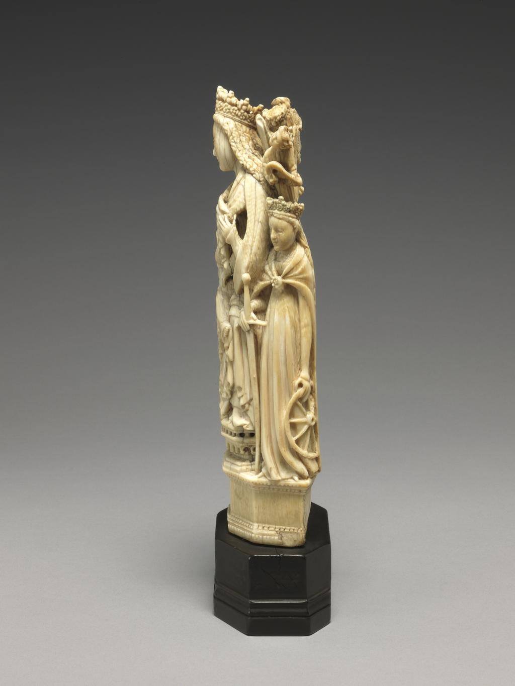 An image of Sculpture / Figure Group. The Virgin and Child with St Dorothy and St Catherine. Virgin and Child seated on a throne with high back, on the top of which stand four small music-making angels. On the left, St Dorothy holding a basket of roses, and on the right, St Catherine with wheel and sword. Carved ivory in the round, height, ivory, 18.9 cm, height, ivory and base, 22.5 cm, circa 1470-1530. German or Spanish.